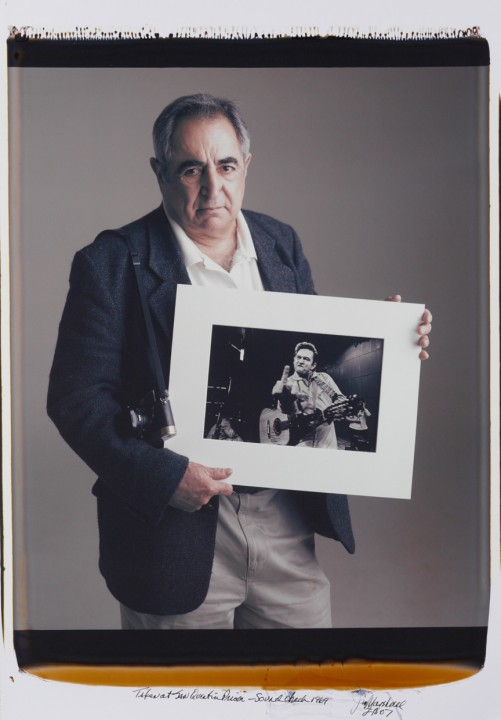 Jim Marshall holding his famous portrait of Johnny Cash, by Tim Mantoani